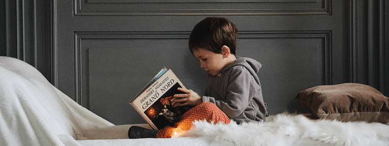 child sitting and reading indoors